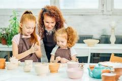 红头发人与黏土,瓦器孩子的母亲和两个女儿模子 免版税库存照片