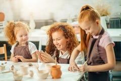 红头发人与黏土,瓦器孩子的母亲和两个女儿模子 图库摄影