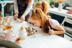 红头发人与黏土,瓦器孩子的母亲和两个女儿模子 免版税图库摄影