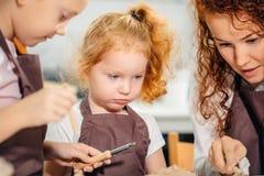 红头发人与黏土,瓦器孩子的母亲和两个女儿模子 库存图片