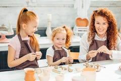 红头发人与黏土,瓦器孩子的母亲和两个女儿模子 免版税库存图片