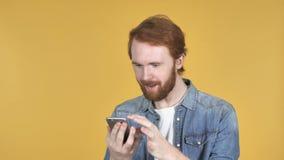 红头发人人浏览智能手机,黄色背景 股票录像