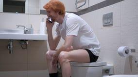 红头发人人谈话在洗手间,洗脸台的电话 免版税库存图片