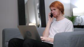 红头发人人谈话在电话,当研究膝上型计算机时 免版税库存图片