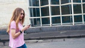 红头发人使用手机的姜妇女在城市街道上的步行期间  股票录像