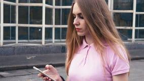 红头发人使用手机的姜妇女在城市街道上的步行期间  影视素材