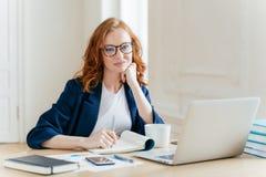 红头发人卷曲妇女办公室工作者分析数据,写认为的报告,在coworking的办公室摆在,改进网上销售,饮料 免版税图库摄影