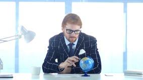 红头发人商人读书与注意的世界地球 免版税库存照片