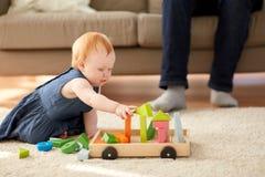 红头发人在家使用与玩具块的女婴 库存图片