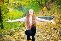 红头发人女孩投掷的叶子在秋天公园 免版税库存图片