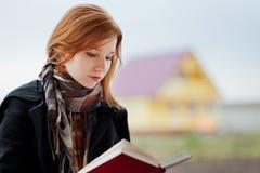 红头发人女孩读取 免版税图库摄影