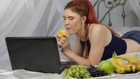 红头发人妇女吃新鲜水果,当在床上时 健康早餐慢动作 股票视频