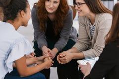 红头发人妇女支持的朋友在精神疗法小组聚会期间 免版税库存图片