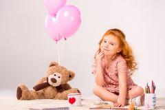 红头发人孩子坐有玩具熊的地毯 免版税图库摄影
