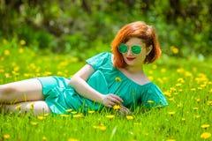 红头发人少妇画象放松在春天公园的 免版税库存图片