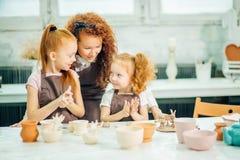 红头发人母亲和孩子女儿从黏土和戏剧一起在家铸造了 库存图片