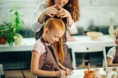 红头发人母亲和孩子女儿从黏土和戏剧一起在家铸造了 免版税库存照片
