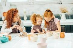 红头发人母亲和孩子女儿从黏土和戏剧一起在家铸造了 库存照片