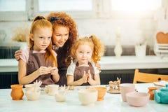 红头发人母亲和孩子女儿从黏土和戏剧一起在家铸造了 免版税库存图片