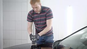 红头发人男性工作者由在车服务的抛光机处理汽车表面,包括由防护层数 股票视频