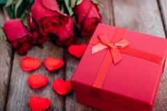 红心、花玫瑰和礼物盒在木背景 免版税库存图片