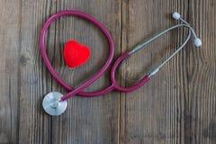 红心和一个听诊器在老木书桌上 水平 免版税图库摄影