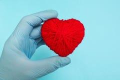 红心在蓝色背景的医生的手上,概念 免版税库存图片