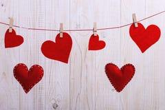 红心垂悬由手工制造的毛毡制成在与别针的一条绳索,概念,横幅,保存空间 库存图片