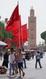 红旗和清真寺在马拉喀什 免版税库存照片
