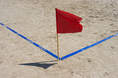 红旗和蓝线在沙子靠岸 免版税图库摄影