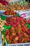 红毛丹在市场摊位的待售 库存图片