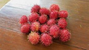 红毛丹是一个甜热带水果 在木桌上的红色成熟红毛丹果子 新鲜水果有很多甜花蜜 免版税库存照片