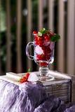 红浆果和冰块在一块透明玻璃在桌上 免版税库存照片