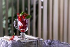 红浆果和冰块在一块透明玻璃在桌上 免版税库存图片