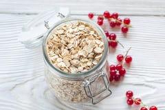 红浆果和燕麦在金属螺盖玻璃瓶剥落 库存图片