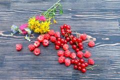 红浆果莓和葡萄在一张木桌上的 免版税库存照片