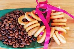 红润百吉卷和咖啡豆在板材 库存照片
