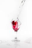 红潮从在白色背景的一个残破的酒杯溢出 免版税库存图片