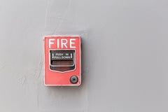 红火在商业buil外部水泥墙壁上的警报开关  免版税库存照片