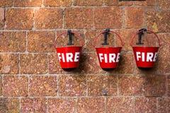 红火容器包含在砖墙背景的沙子 免版税库存照片