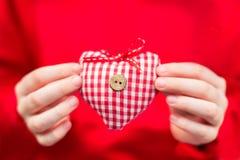 红白的格子花呢披肩纺织品心脏在手上 库存图片