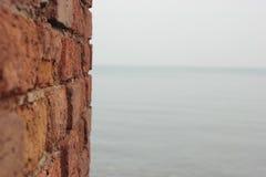 红砖墙壁和海 免版税库存照片