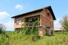 红砖放弃了有残破的窗口和前面铁丝网的家庭房子长满与高未割减的草和履带牵引装置植物 免版税图库摄影