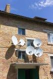红砖有卫星盘板材天线的房子墙壁 免版税库存图片