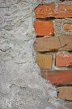 红砖石墙背景特写镜头,破裂的被破坏的灰泥,垂直涂了灰泥灰色灰棕色阻碍石灰石样式的难看的东西 免版税库存照片