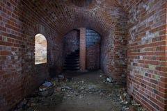 红砖老普鲁士人的堡垒的被成拱形的走廊,结束以一部螺旋形楼梯 图库摄影