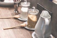 红糖和白糖与牛奶罐在咖啡休息书桌上 库存照片