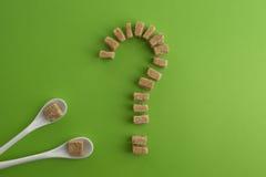 红糖立方体塑造了作为在绿叶背景的一个问号 顶视图 饮食unhealty甜瘾概念 免版税库存照片