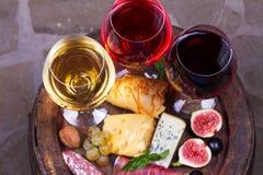 红色、玫瑰色和白色玻璃和瓶酒 乳酪、无花果、葡萄、熏火腿和面包在老木桶 在视图之上 库存照片