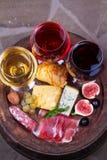 红色、玫瑰色和白色玻璃和瓶酒 乳酪、无花果、葡萄、熏火腿和面包在老木桶 在视图之上 免版税库存图片